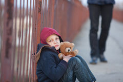 Homeless boy sitting on the bridge Stock Images