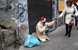 Homeless charity. Woman gives money to homeless with christmas hat, asking charity in the center of Naples, Italy Stock Photo