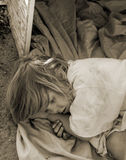 Homeless child laying down in an old box Royalty Free Stock Photos