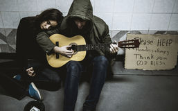 Homeless Couple Man Playing Guitar Asking For Money Donation Stock Photo