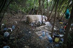 Homeless doweling. Small habitation, tent made from garbage. In dirty littered forest royalty free stock image