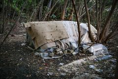 Homeless doweling. Small habitation, tent made from garbage. In dirty littered forest stock image