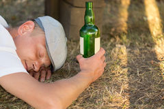 Homeless drunk adult man sleeping on the ground Royalty Free Stock Photo