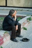 Sad homeless old man. Homeless elderly beggar sitting on the sidewalk Stock Images