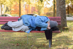 Homeless elderly woman sleeping rough in a park Stock Images