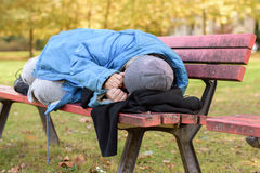 Homeless elderly woman sleeping rough in a park Royalty Free Stock Photography