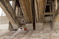 Homeless encampment under bridge in Los Angeles. A tent and other belongings of homeless person under a bridge over the Los Angeles River in DTLA. The Los Stock Image