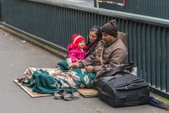 Homeless family sitting on the street royalty free stock photos