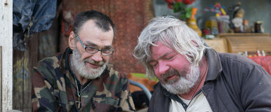 Homeless friends. Slovenly homeless friends with little smile Stock Photos