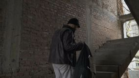 Homeless with garbage bag up stairs in abandoned building. Sick homeless with garbage bag up stairs in abandoned building. Young bum in dirty torn clothes walks stock footage