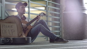 Homeless guitarist hipster playing for money stock footage