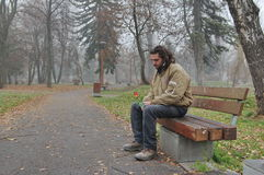 Homeless and hoping for miracle. A thoughtful sad homeless young man sitting on a bench in the park with a beautiful rose in hands, and hoping for a miracle Stock Photos