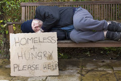 Homeless hungry. Hobo sleeping and begging on park bench stock image