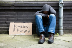 Homeless And Hungry Man. Sitting On Street With Signboard stock images