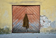 Homeless jacket on an Old Door. Old jacket hanging on a square door in an old wall with no people Royalty Free Stock Photos