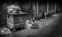 Homeless Jobs !. This photo of a woman looking for some staff in the garbage to sell them and to live Stock Image
