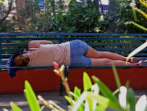 Homeless or just Dozing?. Young Woman Asleep on Park Bench Royalty Free Stock Image