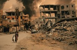 Homeless little girl walking in destroyed city stock photo