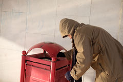 Homeless looking for food in the garbage bin Stock Images