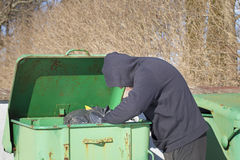 Homeless looking for food. In waste containers Royalty Free Stock Images