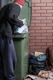Homeless looking for something in the trash Royalty Free Stock Photo