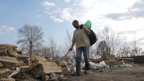 Homeless male searching for plastic at trash site. Front view of senior homeless male holding trash bin bags, walking and searching for materials to recycle at stock footage