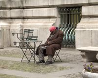 Homeless Man. This is a shot of a homeless man napping on a chair in front of a public building in New York City stock photos
