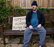Homeless man. Begging on park bench royalty free stock image
