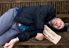 Homeless man. Homeless drunk man sleeping on bench stock photo