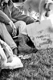 Homeless man. By hungry dog stock image