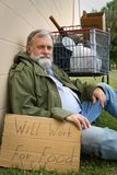 Homeless Man. Rests leaning against a wall hold a sign with his possessions in a grocery cart Stock Photo