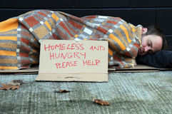 Homeless man. Homeless may sleeps on sidewalk under blanket on cold autumn day Royalty Free Stock Images