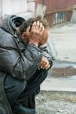 Sad homeless man in depression. Sad homeless beggar in depression sitting on a street Stock Photography