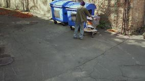 Homeless man approaching trash can in the street. stock footage