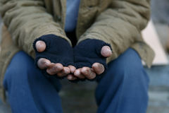 Homeless man asking for help. Man in need. Unhappy homeless man is holding hands to get help stock photo
