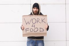 A homeless man with a beard and in a hood stands on the street with a sign about the request for work for food. Outdoor. A homeless man with a beard and in a Royalty Free Stock Images