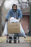 Homeless. Man with beard pushing a shopping cart with all his possessions Royalty Free Stock Image