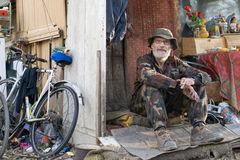 Homeless man. Bearded old homeless man sitting on her poverty Royalty Free Stock Images