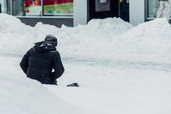 Homeless man begs for alms knees in the snow. Homeless man begging sitting in the snow in Russia stock photo