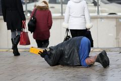 Homeless man begs for money. Homeless man with hurt leg on his knees begs for money at the street. Ten years after joining the EU Bulgaria is still the poorest Stock Images