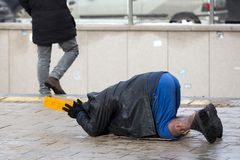 Homeless man begs for money. Homeless man with hurt leg on his knees begs for money at the street. Ten years after joining the EU Bulgaria is still the poorest Royalty Free Stock Photos