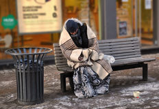Homeless. Man on a bench a cold morning in Odense Stock Image
