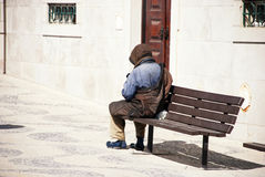 A homeless man on a bench in Lisbon, Portugal. Stock Images