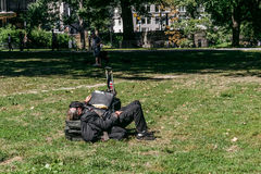 Homeless man in Central Park in New York. New York, USA - September 20, 2015: Homeless man sleeps on the lawn in Central Park in Manhattan Stock Photo
