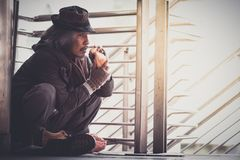 Homeless man on the corner of the walkway street in the city eating bread form kindness people give him royalty free stock photo