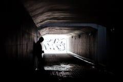 Homeless man in dark tunnel stock image