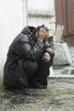 Homeless man in depression. Homeless beggar sitting at the wall on the city street Stock Photos