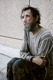 Homeless man in depression. Homeless man sitting on the sidewalk stock photography