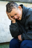 Homeless man in despair. Homeless man in depression on a city street Royalty Free Stock Photos