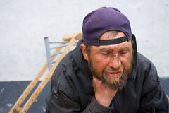Homeless man in despair on the city street Stock Images